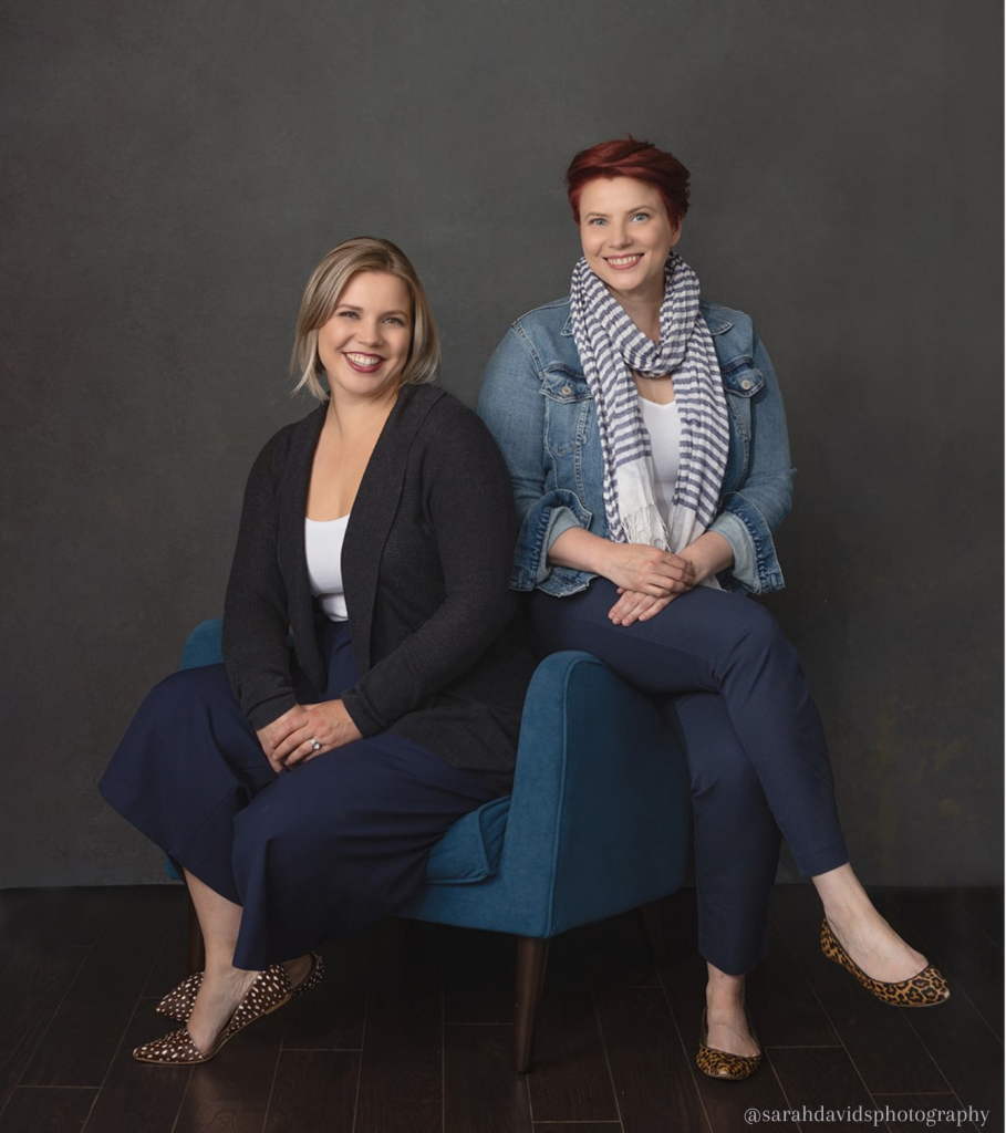 Two white women are sitting in a royal blue armchair against a dark grey background. Sitting in the chair is Sofia, with chin length blonde hair. She is smiling. On the right is Eleonora, sitting on the arm of the chair with her legs crossed and her hands resting in her lap. She has short red hair and is smiling.